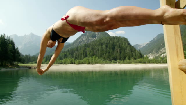 SLOW MOTION CLOSE UP: Young woman jumping into the beautiful mountain lake under the high mountains video