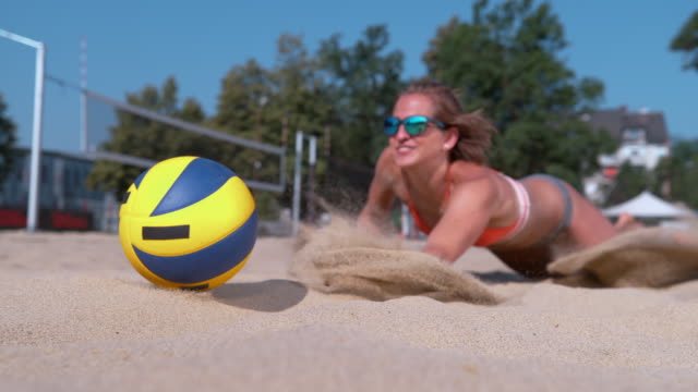 CLOSE UP: Young woman jumps into the sand trying to hit the ball with her hand. SLOW MOTION, CLOSE UP, DOF: Fit young Caucasian woman jumps into the sand trying to hit the ball with her hand during a beach volleyball tournament. Athletic girl fails to save a point during game. volleyball sport stock videos & royalty-free footage