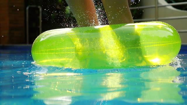 stockvideo's en b-roll-footage met jonge vrouw springt op opblaasbare ringen in zwembad. opspattend water in slow motion. 1920 x 1080 - opblaasband
