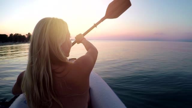 junge frau kajak am ägäischen meer bei sonnenuntergang - kanu stock-videos und b-roll-filmmaterial