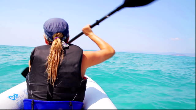 Young woman kayaking on sea video