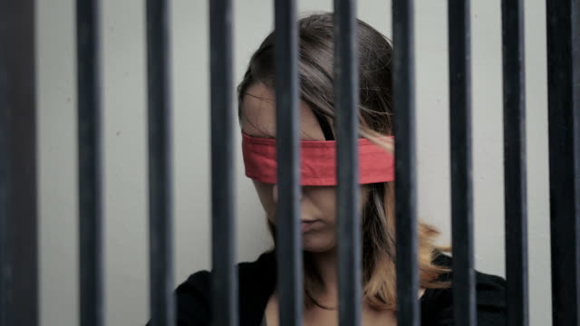 young woman kidnapped and imprisoned in a cell, blindfolded Close up on young woman kidnapped and imprisoned in a cell, blindfolded human trafficking stock videos & royalty-free footage