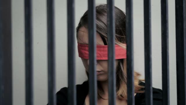vídeos y material grabado en eventos de stock de joven secuestrado y encarcelado en una celda, con los ojos vendada - human trafficking