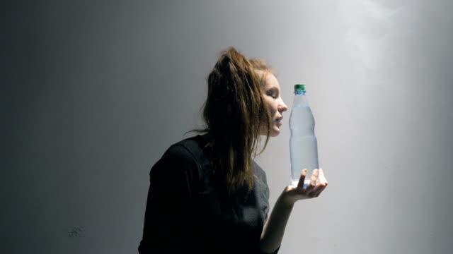 Junge Frau küsst eine Flasche Wasser – Video