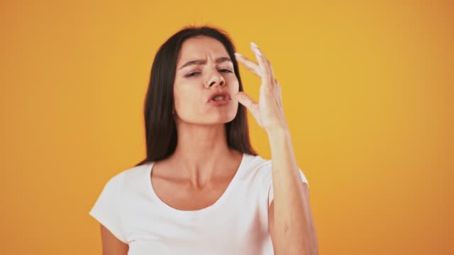 vídeos de stock e filmes b-roll de young woman kissing her fingers and showing tasty gesture, posing against orange background - comida pronta