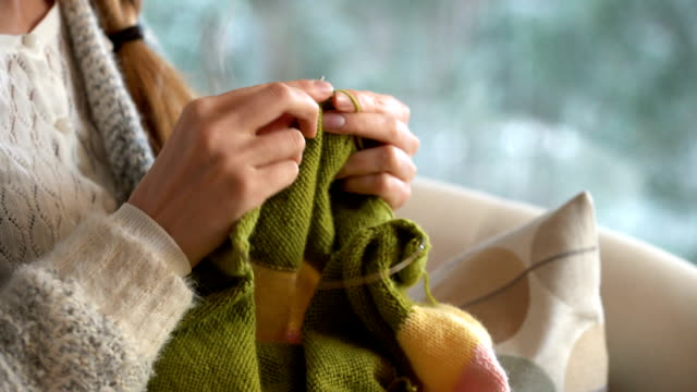 Young woman knitting warm wool sweater in the sitting room against snow landscape from outside