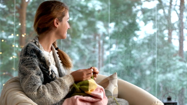 Young woman knitting warm wool sweater in the sitting room against snow landscape from outside video