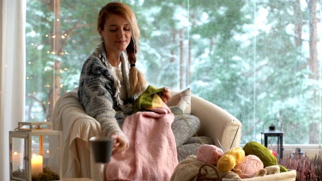 若い女性から外の雪景色とシッティング ルームで暖かいウールのセーターを編む - 田舎のライフスタイル点の映像素材/bロール