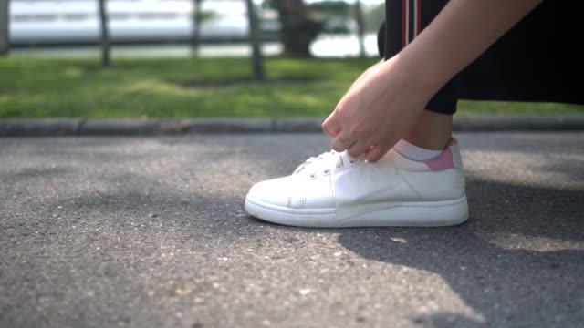 stockvideo's en b-roll-footage met jonge vrouw lace up snickers en gaan - running shoes