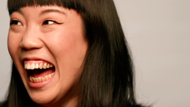 Young woman laughing against white background video