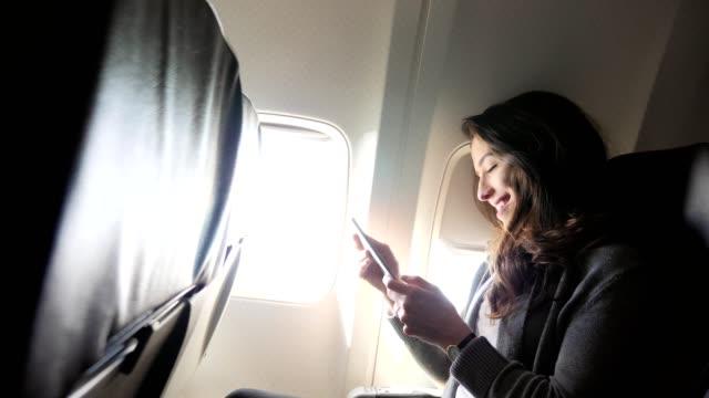 ung kvinna skrattar när man använder smartphone under flygning - affärsresa bildbanksvideor och videomaterial från bakom kulisserna