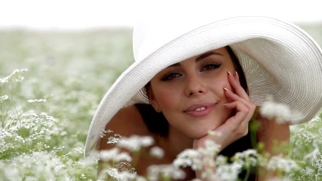 Young Woman Laying In a Field Smiling Face Of a Young Woman In a Blossoming Field. Looking At Camera sideways glance stock videos & royalty-free footage