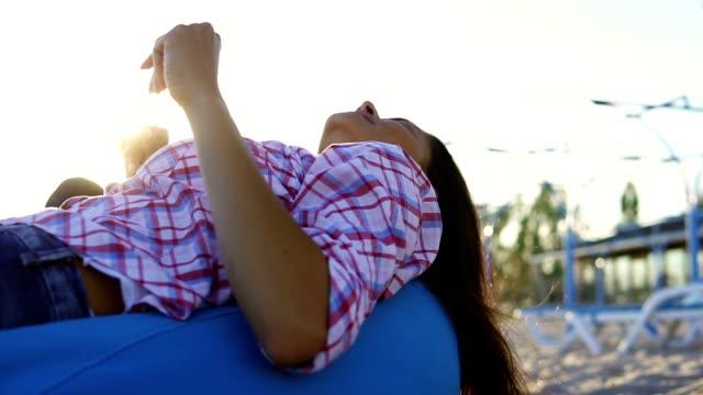 vidéos et rushes de jeune femme portant sur fauteuils et écouter un homme jouant de la guitare parmi le groupe d'amis assis sur la plage et de chanter pendant un coucher de soleil, un soir d'été. slow motion shot - allongé sur le dos