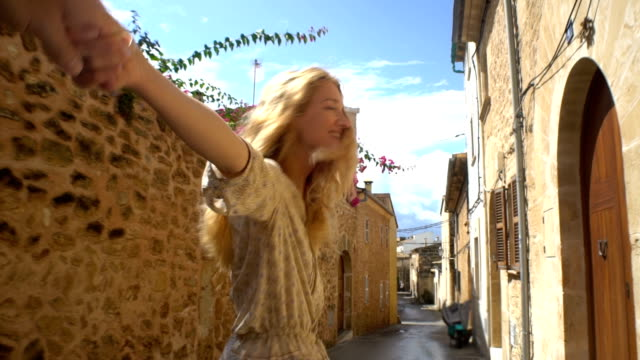 Young Woman Leading a Man to the Adventure in an Old European Town Follow me. Young Woman Leading a Man to the Adventure in an Old European Town. only young women stock videos & royalty-free footage