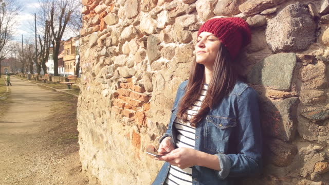 Young woman leaning against a wall in the park.
