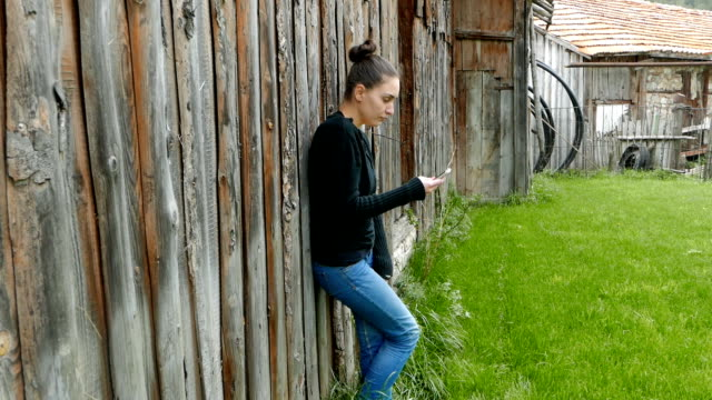 Young woman leaning on a barn and using her smart phone video