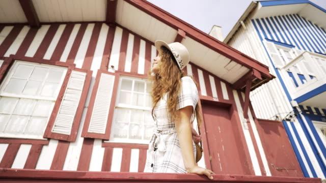 vídeos de stock e filmes b-roll de young woman leaning on balcony handrail - aveiro