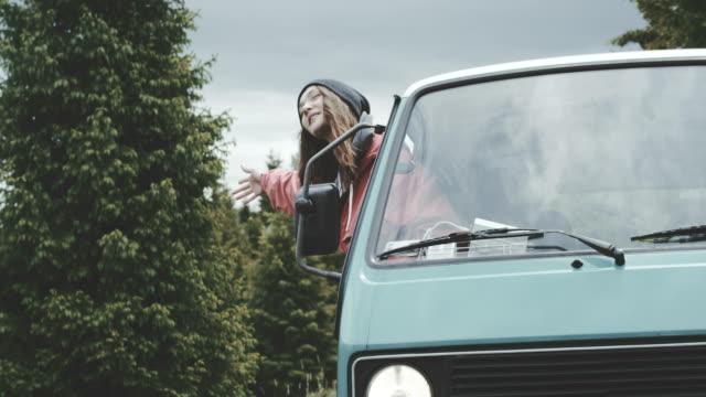 傾いてバンの窓から手を振っている若い女性。 ビデオ
