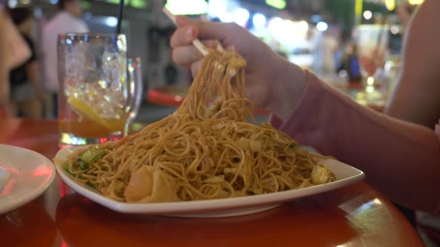 vídeos de stock e filmes b-roll de close up: young woman learning to eat asian noodle dinner with wooden chopsticks - comida asiática