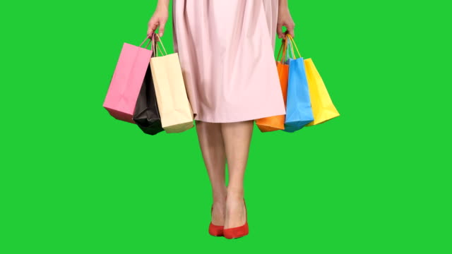 Young woman legs carrying colorful shopping bags on a Green Screen, Chroma Key Medium shot. Young woman legs carrying colorful shopping bags on a Green Screen, Chroma Key. Professional shot in 4K resolution. 005. You can use it e.g. in your commercial video, business, presentation, broadcast dress shoe stock videos & royalty-free footage