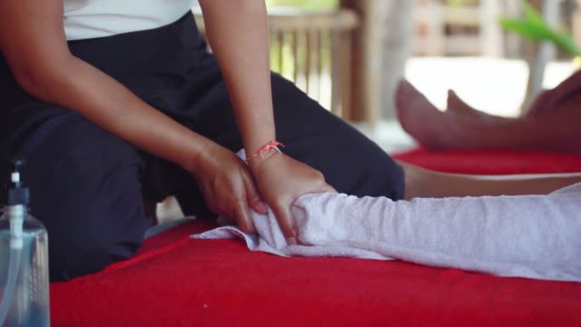 Young woman lies in spa saloon on the tropical beach. Massage therapist doing legs massage. Close up. 1920x1080 Beautiful woman lies in spa saloon on the tropical beach. Massage therapist doing legs massage. 1920x1080, hd baby booties stock videos & royalty-free footage