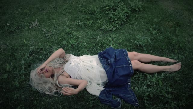 Young woman lies on the grass Young woman lies on the grass. Blonde female slowly rolls on the ground. Freaky unusual girl is touching hair eyes closed videos stock videos & royalty-free footage