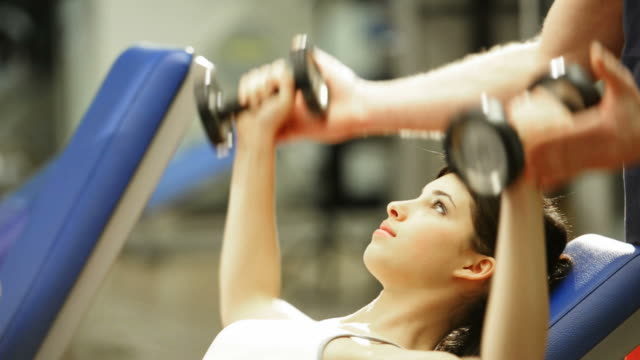 Young Woman Lifting Weights With Coach; HD Photo JPEG video