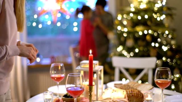 una giovane donna accende le candele al tavolo di natale - pranzo di natale video stock e b–roll