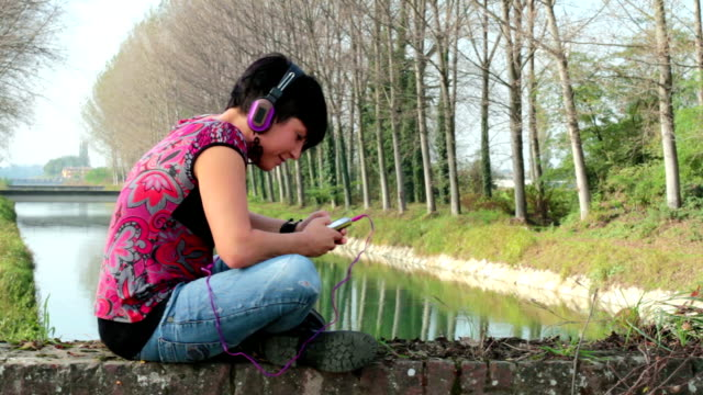 Young woman listen music using headphones video