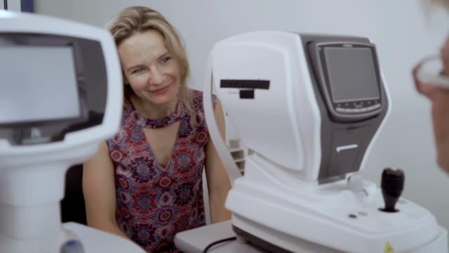 vidéos et rushes de jeune femme écoute oculist après avoir vérifié sa vue sur un équipement moderne - rétine