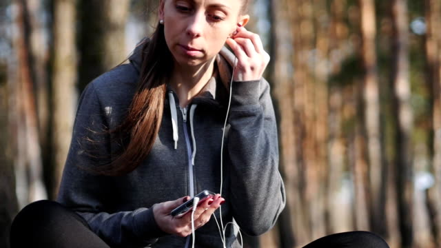Young woman listen to music on her smartphone in the woods. video
