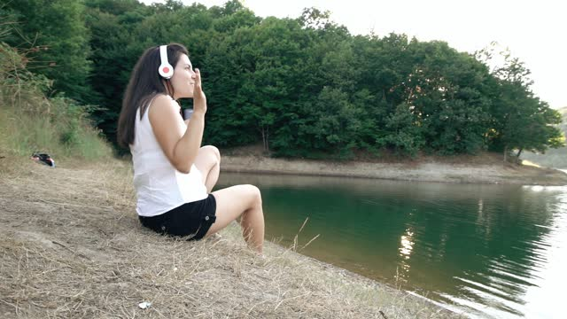 Young woman listening music on headset by the lake