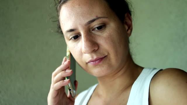 junge frau hören sie mobiltelefon - abwarten stock-videos und b-roll-filmmaterial