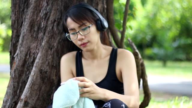 genç kadın bluetooth mezartaşı--dan sonra egzersiz müzik - bluetooth stok videoları ve detay görüntü çekimi