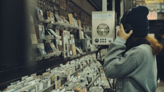 Young woman listening to music in music store