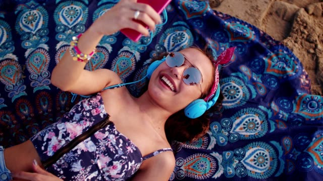 young woman listening to music on headphones at the beach - woman chat video mobile phone video stock e b–roll