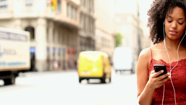 Young woman listening to music on her smart phone. Standing in the street with traffic.