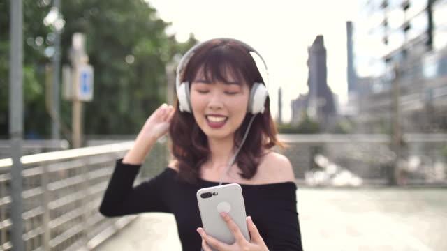 vídeos de stock, filmes e b-roll de uma mulher nova que escuta a música - somente japonês