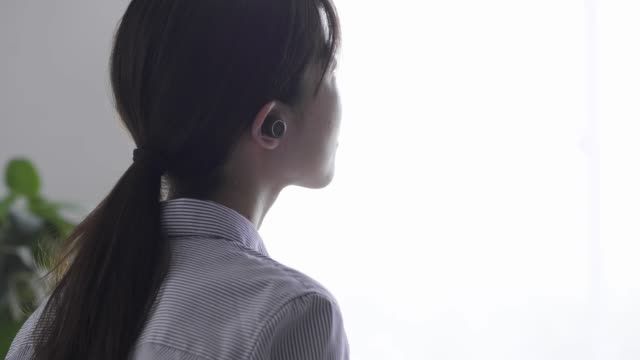 young woman listening to music with wireless earphones - auricolari wireless video stock e b–roll