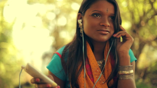 Young woman listens to music through the smartphone and earphones in nature.