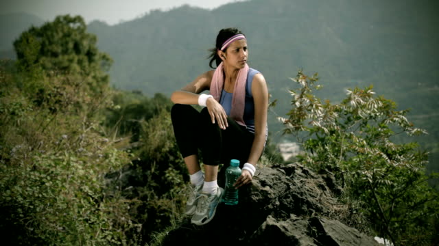 Young woman listing music after fitness exercise in nature video