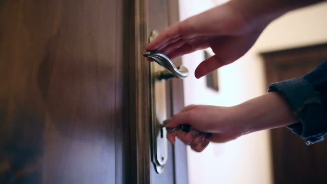 Young woman locking the door close up. video