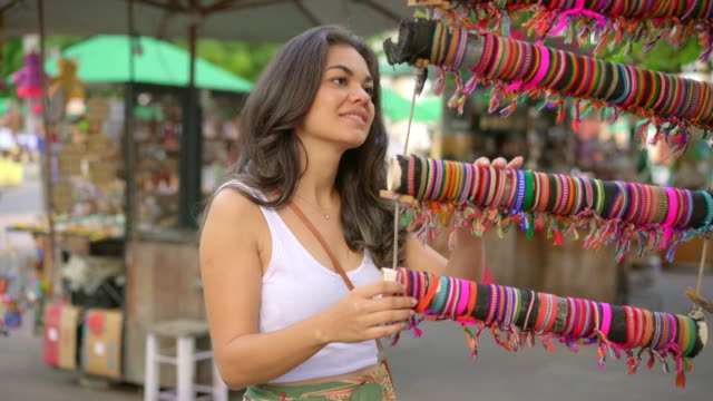 young woman looking and choosing crafts at olinda fair - prodotto d'artigianato video stock e b–roll