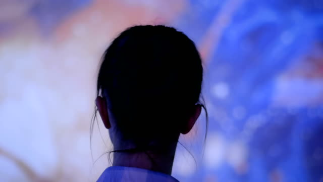 young woman looking around at modern immersive exhibition - museo video stock e b–roll
