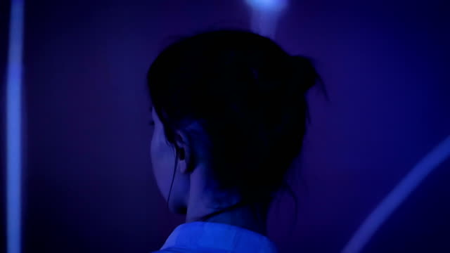 Young woman looking around at modern immersive exhibition