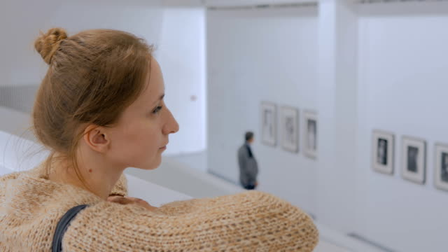 Young woman looking around in modern photo gallery Young woman looking around in modern photo gallery. Education and entertainment concept exhibition stock videos & royalty-free footage