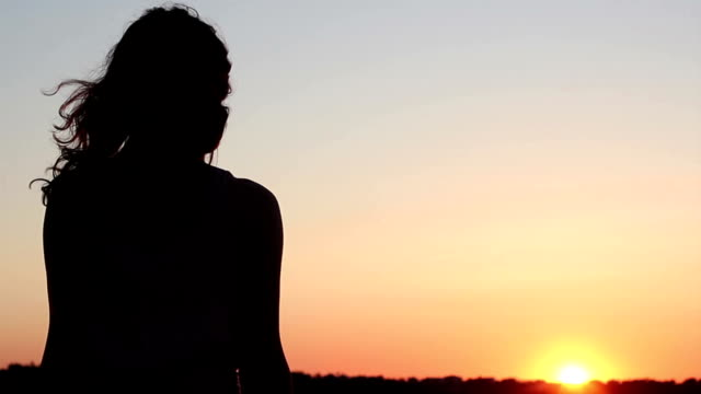 Young woman looking at amazing orange sunset on horizon, thinking video