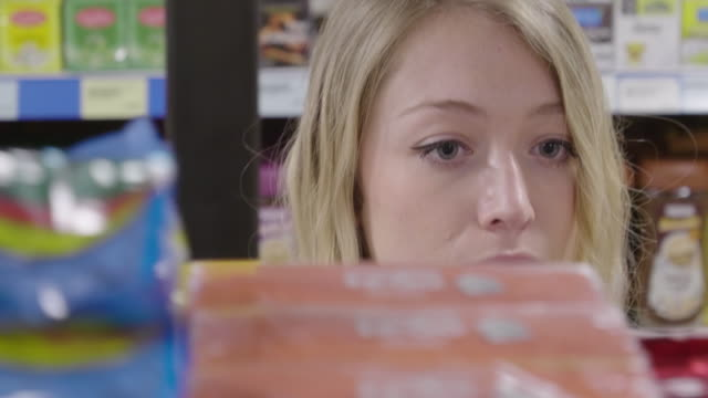 vídeos de stock e filmes b-roll de ds young woman looking at products in a grocery store - ingrediente