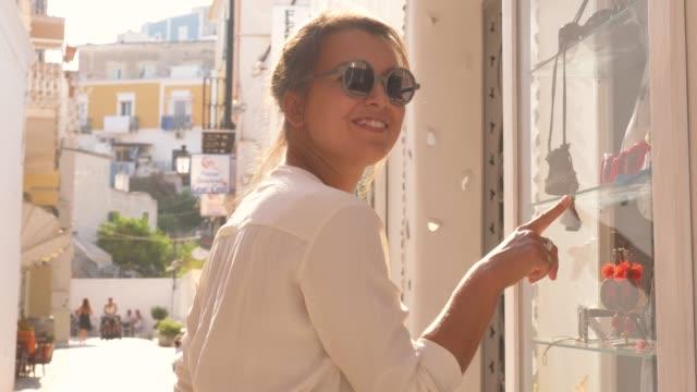 junge frau schaut auf das schaufenster in einer gasse auf der insel ponza, italien. mode bunte kleid rock, sonnenbrille, großen hut. - schaufenster stock-videos und b-roll-filmmaterial