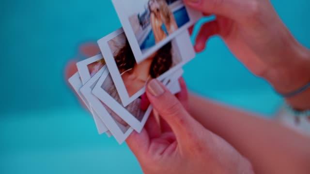 stockvideo's en b-roll-footage met jonge vrouw kijken naar zomer herinneringen direct foto's bij zwembad - polaroid